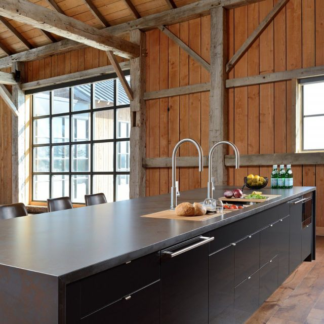 The perfect place for entertaining.   This wine bar in a century old barn features a 7' galley workstation, galley taps, and edge pulls to keep the cabinet fronts clean.  Swipe to zoom out ➡  Courtesy of Elmwood dealer @aurorakitchens Featuring Elmwood cabinetry: Anthracite High Gloss PET, Odessa door style . . . #Elmwood #ElmwoodCabinets #ElmwoodCabinetry #CustomCabinets #CustomCabinetry #LuxuryDesign #InteriorDesign #KitchenDesign #BathDesign #CustomDesign